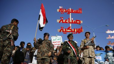 """Houthi fighters hold a red banner that reads """"Saudi Arabia is American made""""."""