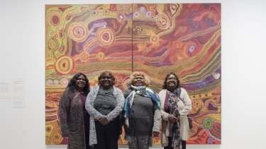 Wynne Prize winners The Ken family's <i>Seven Sisters</i> in front of their work at the Art Gallery of NSW.