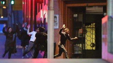 Hostages flee the Lindt Cafe during the siege on December 15, 2014.