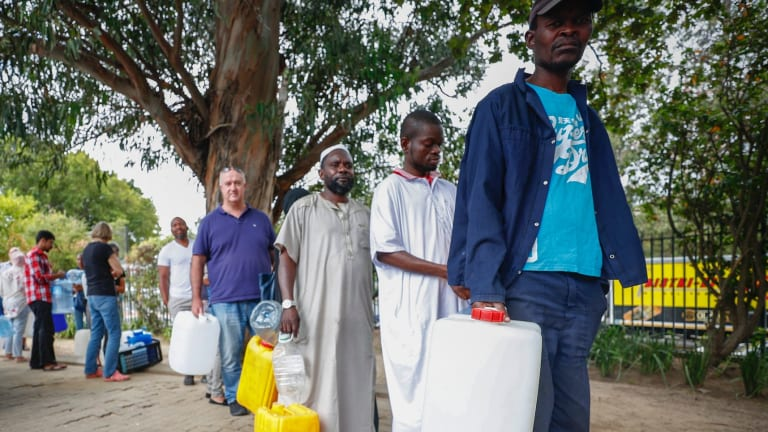 Residents of Cape Town wait in line to collect drinking water from a mountain spring collection point.