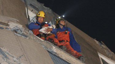 Rescue workers carry a baby swaddled in a cloth from the rubble of a toppled building.