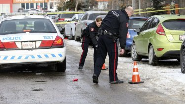 Calgary police place crime scene markers on a street were seven people were shot in a New Year's house party in Killarney.