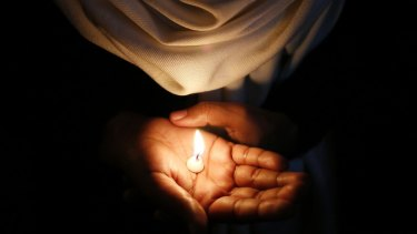 A Christian holds a candle during a vigil.