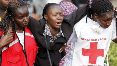 A relative is helped by Kenya Red Cross staff after visiting Nairobi's Chiromo Mortuary to identify bodies of students killed in the April 2 university massacre.