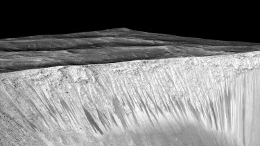 The 'recurring slope lineae' emanating out of the walls of Garni crater on Mars. NASA says the dark streaks are evidence of flowing, briny liquid water.