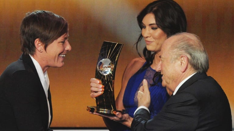 Hope Solo (centre) on stage with Sepp Blatter to present teammate Abby Wambach with the FIFA Women's World Player of the Year award. Solo claims she was assaulted before walking on stage.