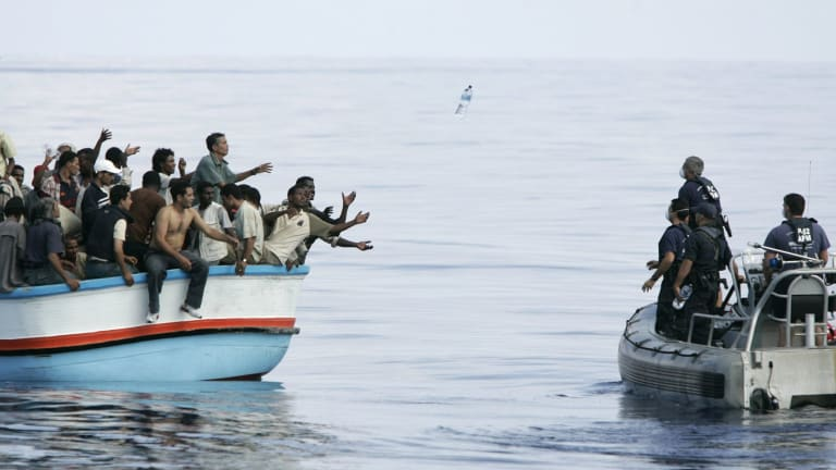 Armed Forces of Malta marines toss bottles of water to a group of about 180 illegal immigrants southwest of Malta.