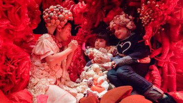 Lily and Nina Vujovic sit beside artist Hiromi Tango inside her art installation the Red Room.
