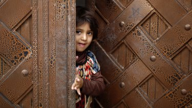 A Yemeni child stands at a door as she waits to receive a polio vaccination during a house-to-house immunisation campaign in Sanaa.