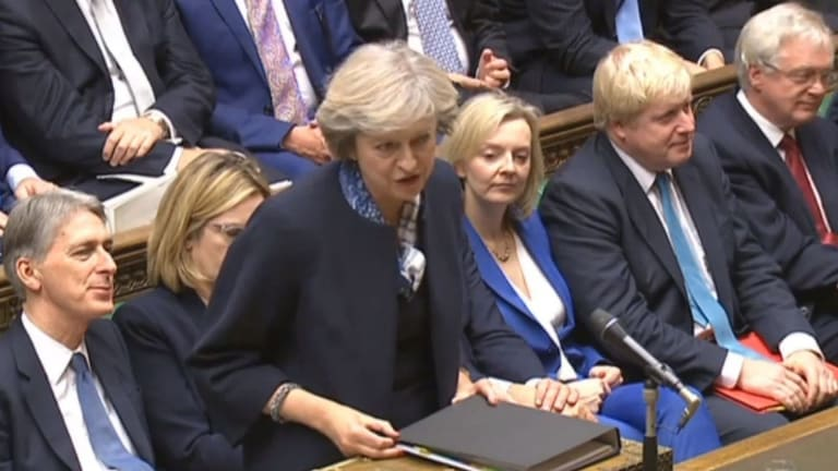 Britain's Prime Minister Theresa May, centre, stands to answer a question during Prime Minister's question time in the Commons.