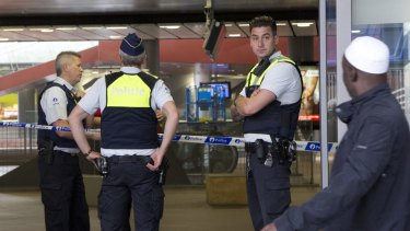 A man walks past police guarding a cordon at Antwerp Central train station in Belgium.