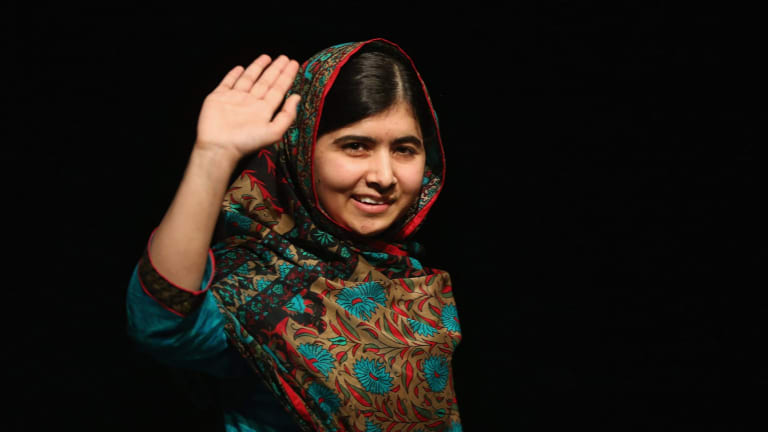 Malala Yousafzai waves to the crowd at a press conference at the Library of Birmingham after being announced as a recipient of the Nobel Peace Prize, on October 10, 2014 in Birmingham, England.