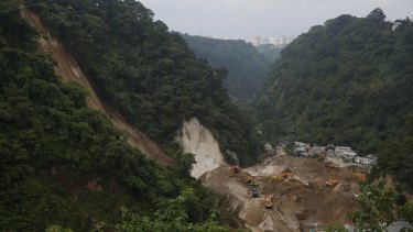 Bulldozers move land on Tuesday to search for victims of the fatal mudslide.