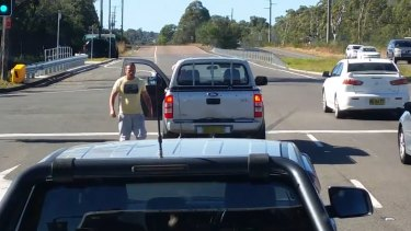 The man walks back to his vehicle after confronting the woman on the NSW central coast.