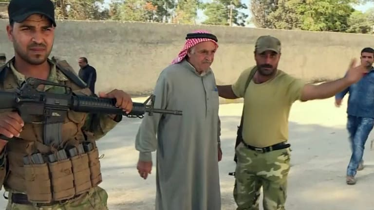 Turkish-backed Syrian opposition forces allow a man to pass after being searched in Dabiq, Syria.