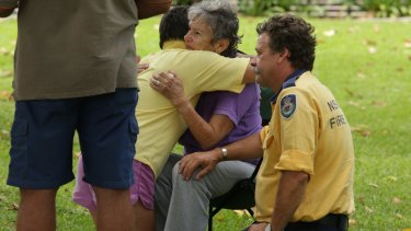 People comfort a woman who escaped an apartment in the marina building as it collapsed.