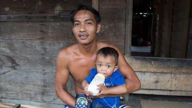 Tengku Antonia bottle feeds his son Tengku Ayuan Kuadi outside his home in Pelalawan village, in Riau province.