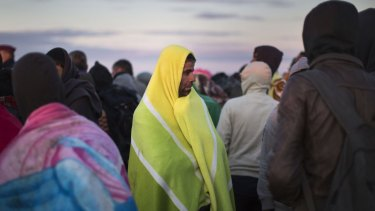 Migrants who had crossed the Serbian border into Hungary the previous evening try to keep warm at dawn in Morahalom, Hungary.