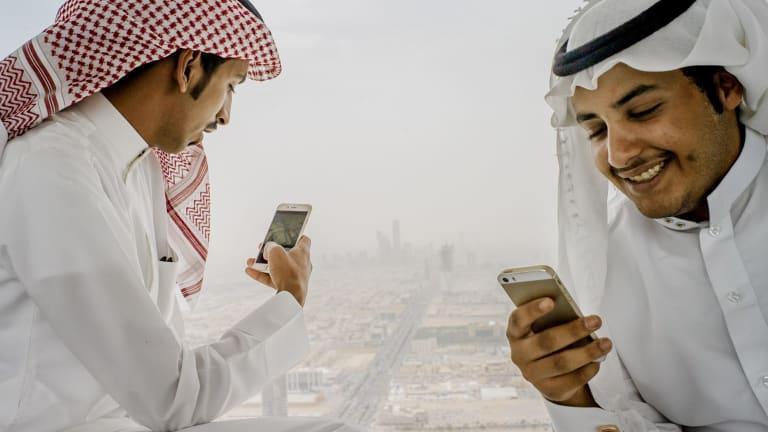 Men use their phones on the skybridge of Kingdom Tower in Riyadh, Saudi Arabia.