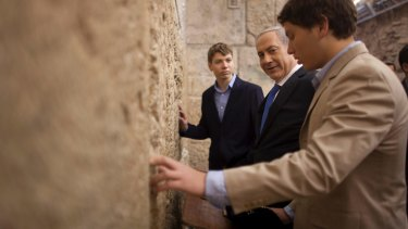 Israeli Prime Minister Benjamin Netanyahu, centre, prays with his sons Yair, background, and Avner, right, in Jerusalem's Old City.