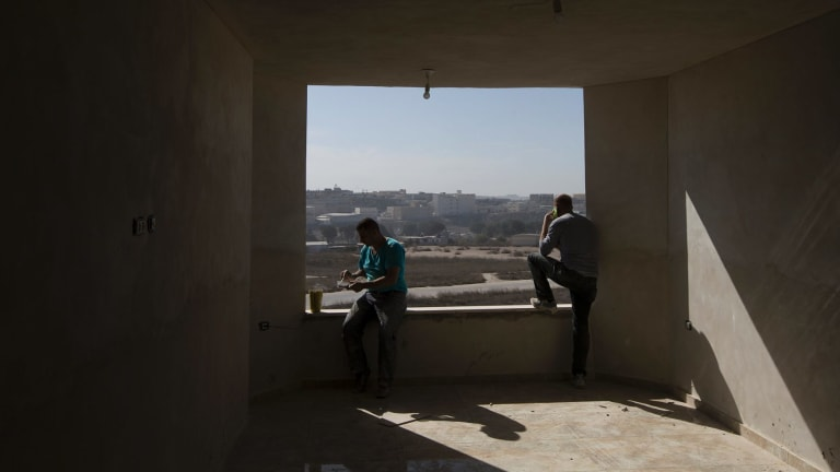 Palestinian workers look out from a building under construction in Kufr Aqab.