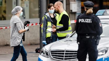 Police officers secure evidence in front of the supermarket in Hamburg.
