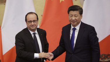 French President Francois Hollande, left, shakes hands with China's President Xi Jinping during a visit to Beijing.