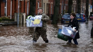 A member of the armed forces helps a resident move their belongings through the floods in Carlisle, north west England.