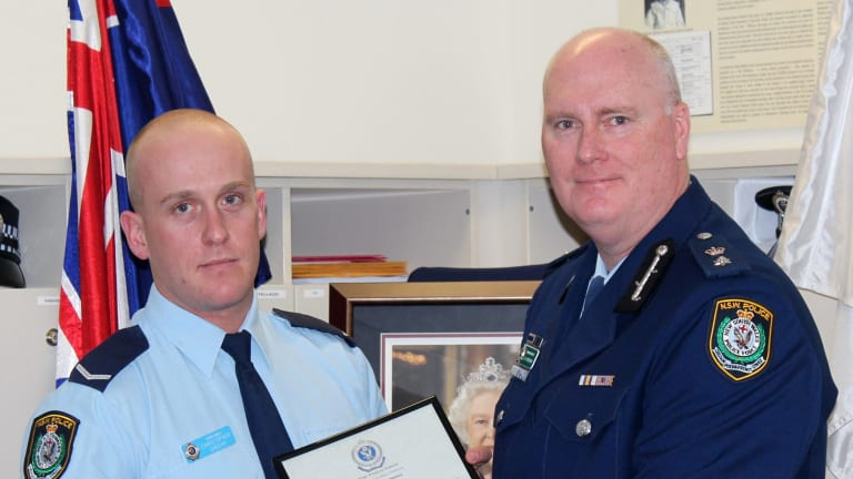 Chris Sheehy (left) receives a bravery award from Newtown Police Commander Simon Hardman in September 2015. Mr Sheehy was under investigation for alleged drug taking after a complaint by Mr Hardman.