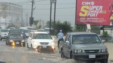 Cars drive along a street under heavy rain in downtown Kingston, Jamaica.