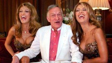 Playboy Magazine founder Hugh Hefner poses with January 2000 Playmates Carol, left, and Darlene Bernola,