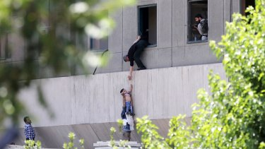 A child is lowered from a window in the Iranian Parliament building following the attack.