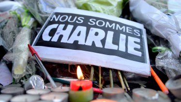 Tributes of drawings, flowers, pens and candles are left in front of the Charlie Hebdo offices following the attack.
