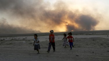 Smoke rises as children flee during clashes between Iraqi security forces and IS members.