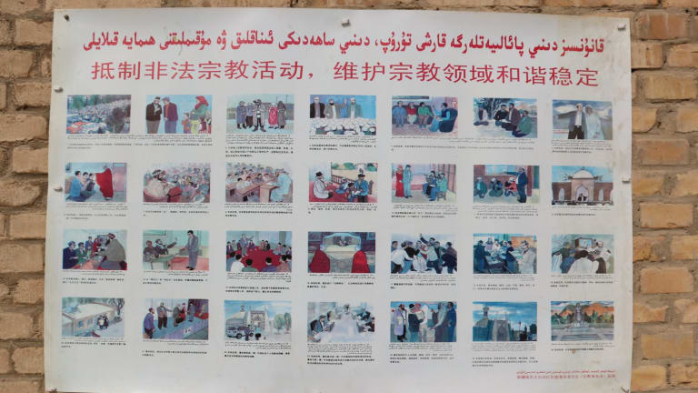 A poster at a mosque in the Xinjiang village of Kuibagh in 2014 shows banned religious practices. A patchwork approach to enforcement has prompted the new law.