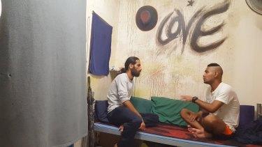 Behrouz Boochani, left, interviews a fellow asylum seeker in <i>Chauka, Please Tell Us the Time</i>.