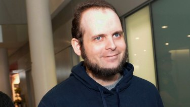 Joshua Boyle is escorted by authorities at Toronto's Pearson International Airport on the family's return in October.