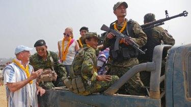Mr Simpkins (left) speaks to Karen guerrillas at the Karen Revolution Day event.