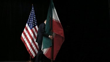 A staff member removes the Iranian flag from the stage after a group picture with foreign ministers and representatives of Unites States, Iran, China, Russia, Britain, Germany, France and the European Union during the Iran nuclear talks at the Vienna International Center in Vienna, Austria Tuesday July 14, 2015.  After 18 days of intense and often fractious negotiation, world powers and Iran struck a landmark deal Tuesday to curb Iran's nuclear program in exchange for billions of dollars in relief from international sanctions ? an agreement designed to avert the threat of a nuclear-armed Iran and another U.S. military intervention in the Muslim world. (Carlos Barria, Pool Photo via AP)