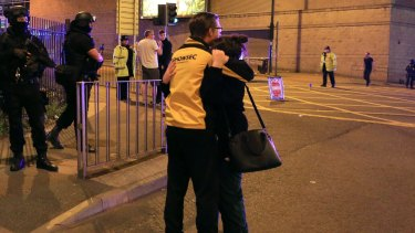 A woman is consoled outside Manchester Arena following the explosion.