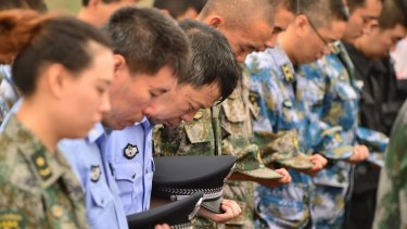 Representatives of People's Liberation Army and public security mourn the dead in Tianjin.