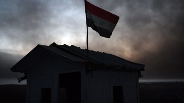 Smoke from an oilfield that was set aflame by retreating ISIS fighters ahead of the Mosul offensive hovers over an Iraqi checkpoint on on October 21.