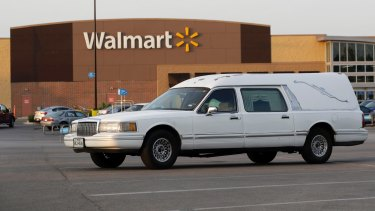 A hearse sits in the parking lot of a Walmart store where eight people were found dead.