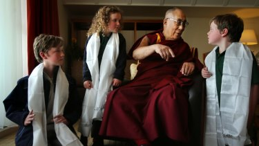 His Holiness the Dalai Lama  talks with Leura public school students Harry Skeggs 11 (left), Eliza Skeggs, 6, and Joe Skeggs, 9.