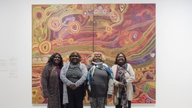 The Ken family in front of their Wynne Prize-winning work, Seven Sisters.