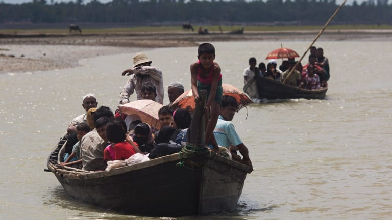 Myanmar's Rohingya cross a stream on Bangladesh side of the border near Cox's Bazar's. Tens of thousands more people have crossed by boat fleeing persecution in Myanmar.