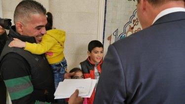 Peter Dutton hands a visa to refugee family member Marwan Alkhdah
