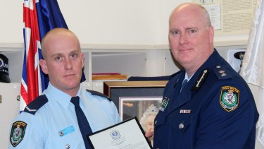 Chris Sheehy (left) receives a bravery award from Newtown Police Commander Simon Hardman in September 2015. The young officer was being covertly monitored during the same period on the recommendation of his boss.