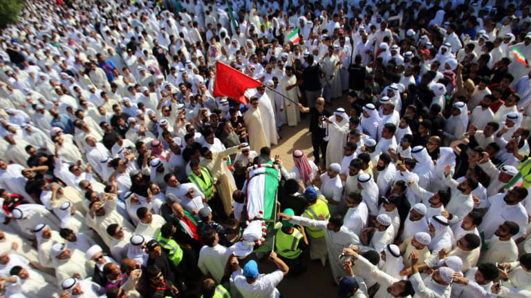 Mourners carry the body of one of the victims of the Al-Imam Al-Sadeq mosque bombing, during a mass funeral at Jaafari cemetery in Kuwait City.