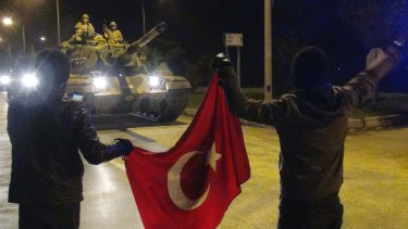 Cheering Turks wave toward tanks heading toward the Syrian border, in Hatay, Turkey.